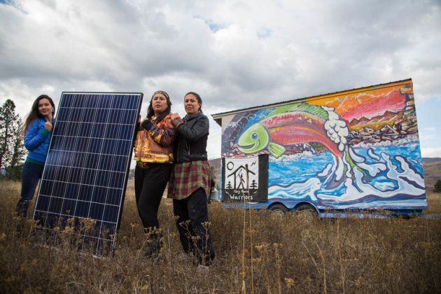 Kanahus Manuel, Mayuk Manuel and Melina Laboucan-Massimo hold the solar panels that have been installed on one of the tiny homes that members of the Secwepemc Nation are building on Kinder Morgan's path through their unceded territory.