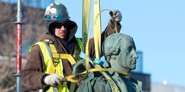 Contractors remove the statue of Edward Cornwallis, a controversial historical figure, in a city park...