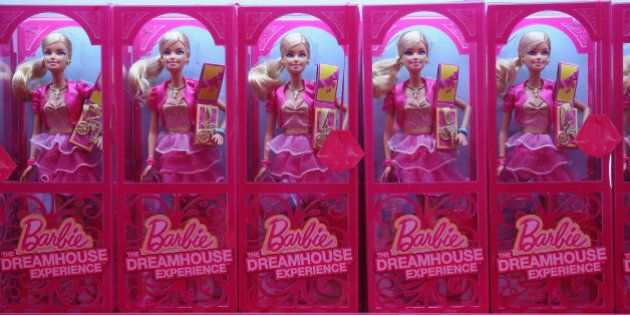 BERLIN, GERMANY - MAY 16: Barbie dolls and other souvenirs line shelves at the merchandising shop at...
