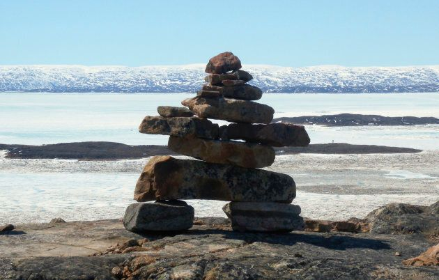 A traditional Inuit inukshuk stone formation looks out over Frobisher Bay near Iqaluit, on June 14,
