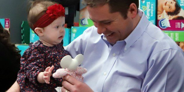 Conservative Party Leader Andrew Scheer plays with 8 month old Ruth Toews prior to announcing that he...