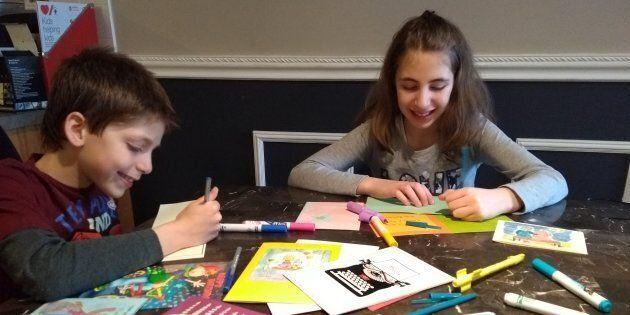 Jeremy and Tamara Cohn, 10, sign cards