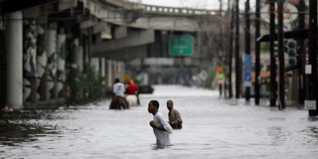 New Orleans residents walk through chest deep floodwater after Hurricane Katrina made landfall on the...