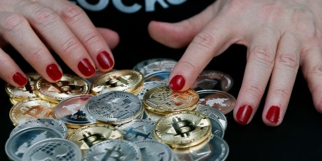 In this photo illustration, a woman shows different visual representations of cryptocurrencies, Ripple,...