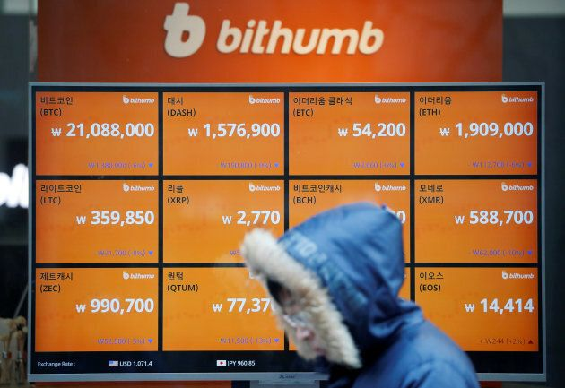 A man walks past an electric board showing exchange rates of various cryptocurrencies at Bithumb cryptocurrencies...