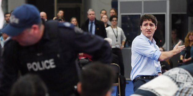 Prime Minister Justin Trudeau argues with a protester as police officers intervene at a public town hall...