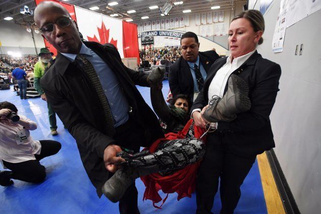 A protester is carried out of the building by police officers during a public town hall with Prime Minister Justin Trudeau (not shown) in Nanaimo, B.C., on Feb. 2, 2018.