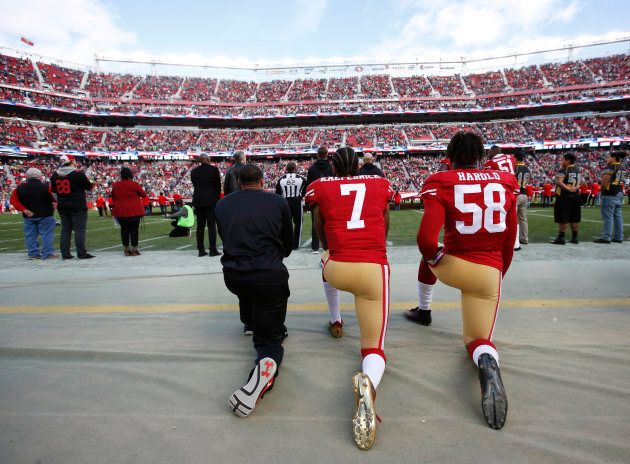 Eric Reid, Colin Kaepernick and Eli Harold of the San Francisco 49ers kneel on the sideline, during the...