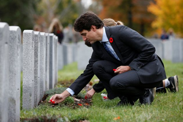 Canada's Prime Minister Justin Trudeau places a poppy at a grave during an event to mark the Veterans'...