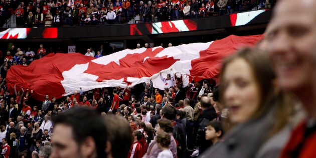 Fans pass around a giant Canadian flag during the singing of the national anthem as the Ottawa Senators...