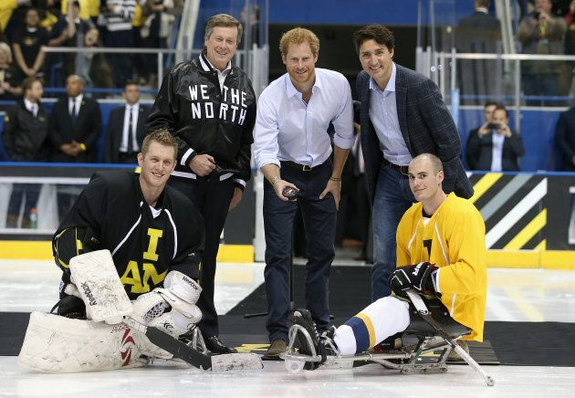 Britain's Prince Harry, left, drops the puck in as Justin Trudeau, right, ahead of the sledge-hockey...