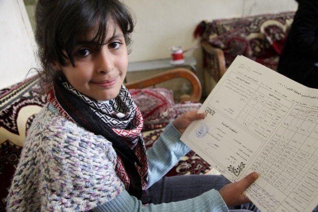 Jouri shows her last report card. Bekaa Valley, Lebanon, 2012.