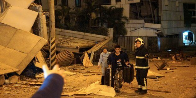 Two guests are escorted by rescue workers from the damaged Marshal Hotel in Hualien, eastern Taiwan early...