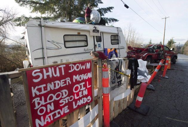 A protester stands on top of a trailer outside the main gates of Kinder Morgan in Burnaby, B.C. on Jan....