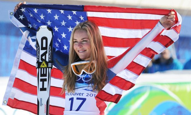 U.S. bronze medallist Lindsey Vonn celebrates with her national flag on the podium during the Vancouver...