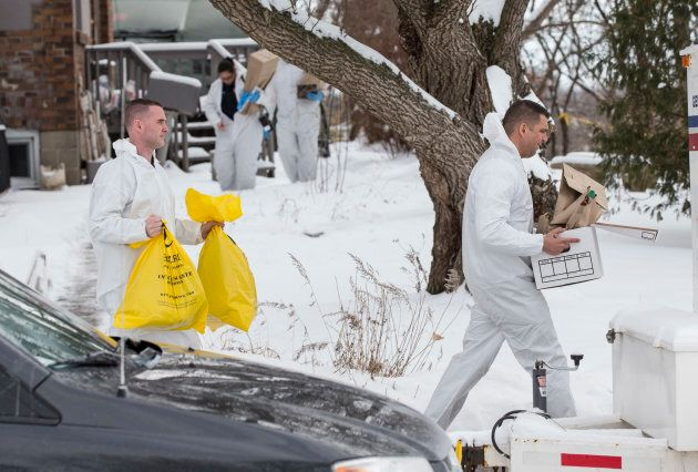 Forensic investigators remove evidence from inside the home at 53 Mallory Cresc. in Toronto on