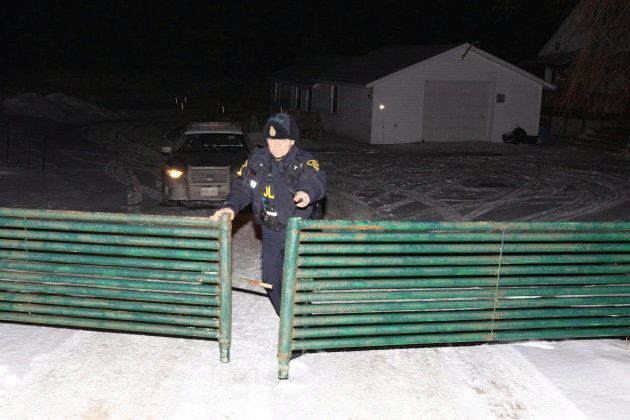 OPP officer closes the gate at the driveway at a property north of Madoc, Ont., on Jan. 18,