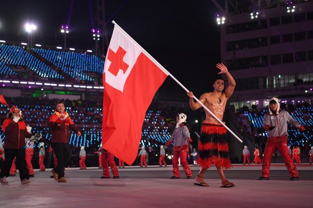 Flag bearer Pita Taufatofua of Tonga leads his country out during the opening