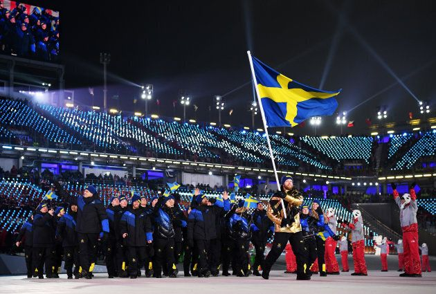 Flag-bearer of Sweden Niklas Edin and teammates enter the stadium during the opening ceremony.