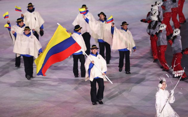 Flag bearer Pedro Causil of Colombia leads the
