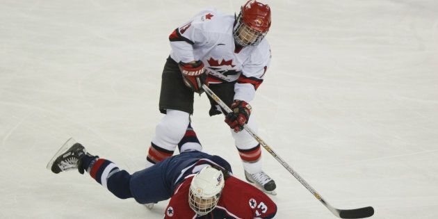 Caroline Ouellette of Canada knocks down Julie Chu of the U.S. during the women's ice hockey gold medal...