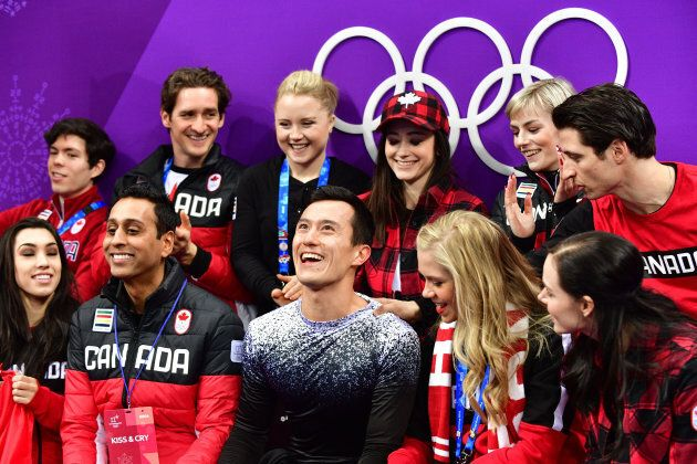 Canada's Patrick Chan, front centre, reacts after competing in the figure skating team event men's single...