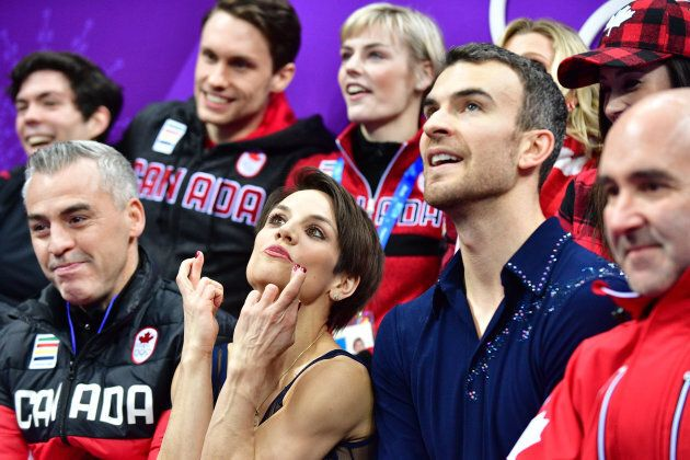 Canada's Meagan Duhamel crosses her fingers as her partner Canada's Eric Radford looks on after competing...