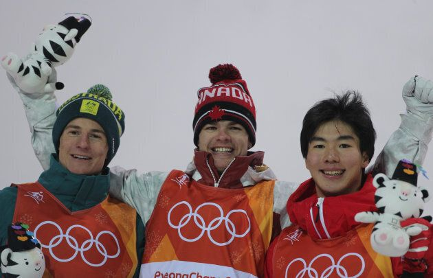 Mikael Kingsbury, centre, celebrates his gold medal win with silver medallist Matt Graham, left and bronze...