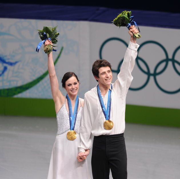 Virtue and Moir pose on the podium after winning the 2010 Winter Olympics ice dance figure skating competition...