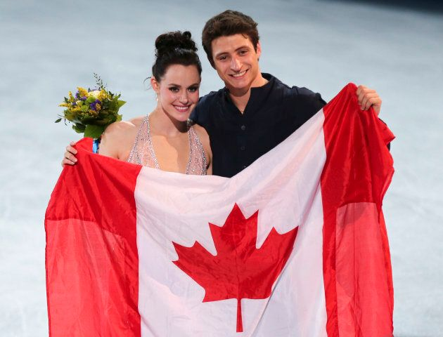Virtue and Moir pose with the Canadian flag after winning silver at Sochi.