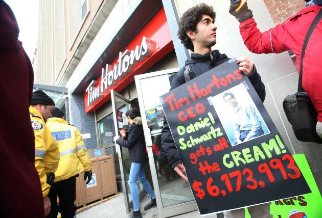 Protesters hold signs outside the Tim Horton's Bloor Street West location, Jan. 10. The rallies were...