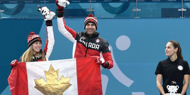 Canada's Kaitlyn Lawes and John Morris celebrate on the podium during the curling mixed doubles venue
