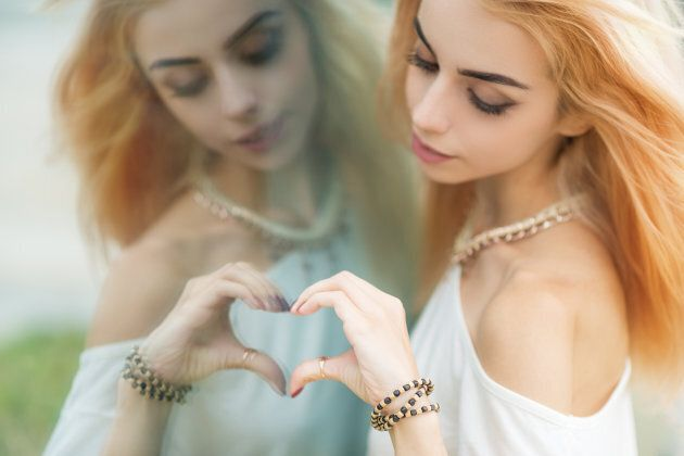 Young beautiful woman making a heart shape by hands in the mirror. Selective soft focus on hand.