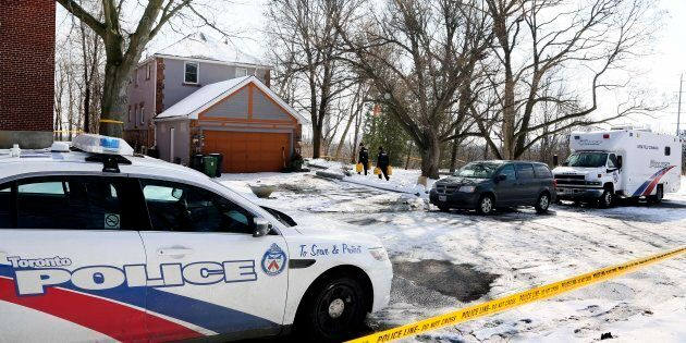 Police carry cans of fuel for investigators at 53 Mallory Cres. in Toronto on Feb. 1,