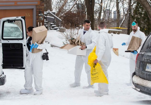 Forensic investigators remove evidence from inside the home at 53 Mallory Cresc. in