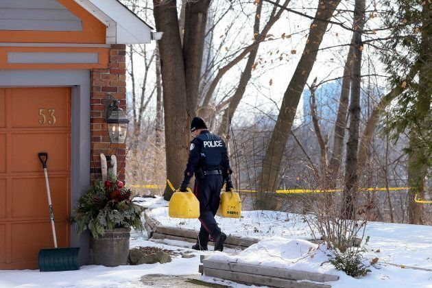 A police officer carries cans of fuel for investigators at 53 Mallory Cres. in Toronto on Feb. 1,