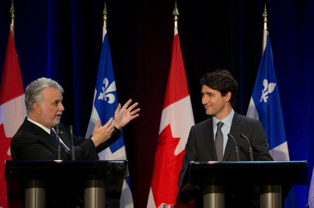 Canadian Prime Minister Justin Trudeau and Quebec Premier Philippe Couillard sign an infrastructure agreement...