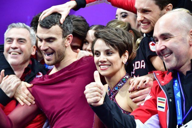 Canada's Meagan Duhamel, centre right and partner Eric Radford, centre left, celebrate with their teammates...
