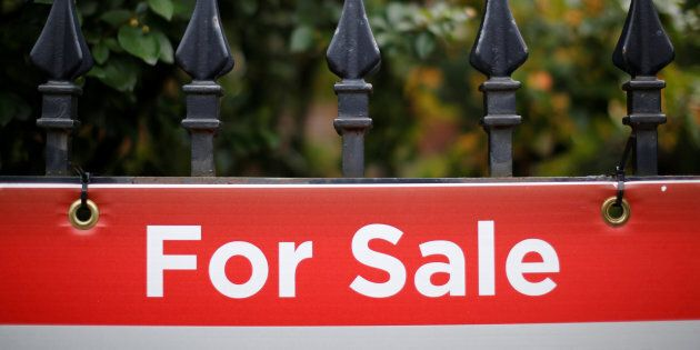 A real estate sign is seen hanging on a fence in front of a house for sale in Ottawa, Ontario, Canada,...