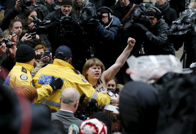 A protester is detained by police after an Ontario judge found Jian Ghomeshi not guilty of five criminal charges in Toronto on March 24, 2016.