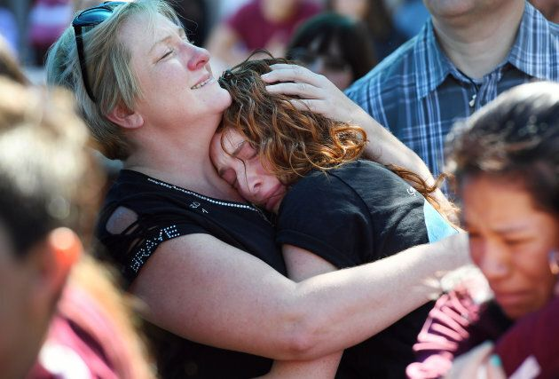 A mother embraces her daughter during a community prayer vigil for Marjory Stoneman Douglas High School...