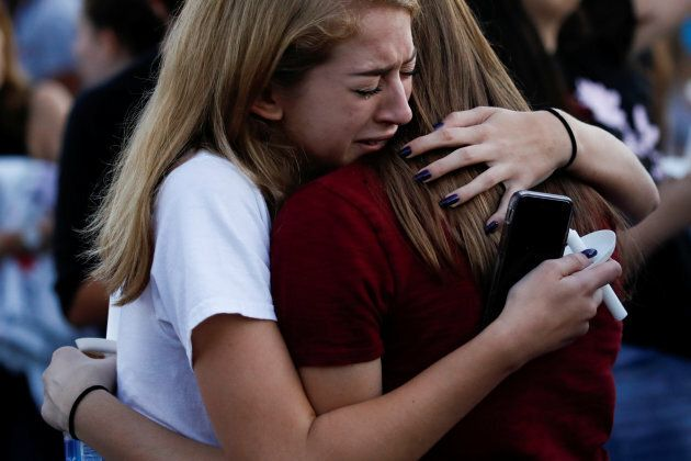 Students mourn during a candlelight vigil for victims the shooting at nearby Marjory Stoneman Douglas High School, in Parkland, Florida, on Feb. 15, 2018.