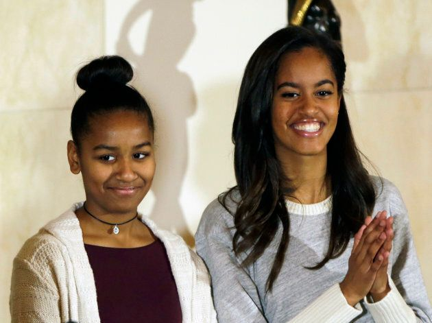 Michelle Obama's daughters Sasha and Malia listen to their father, Barack, during the pardoning of the...