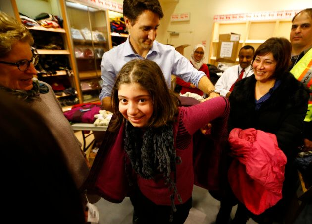 Prime Minister Justin Trudeau helps a young Syrian refugee try on a winter coat after she arrived with her family from Beirut at the Toronto Pearson International Airport in Mississauga, Ont., on Dec. 11, 2015.