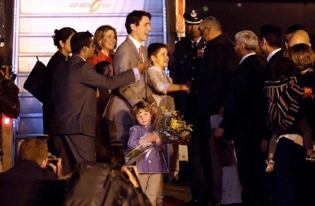 Justin Trudeau's son, Hadrien, walks with a bouquet of flowers as his parents greet Indian and Canadian...