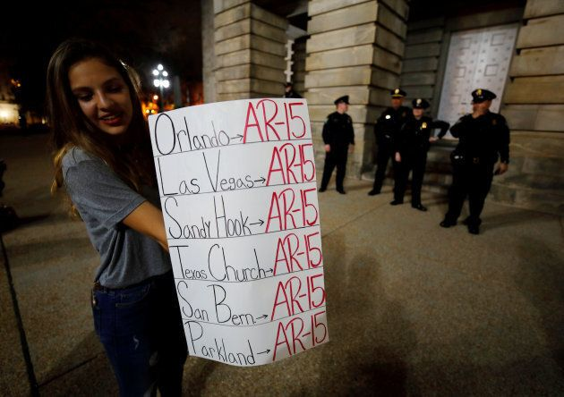 A student holds a sign noting the use of the AR-15 automatic rifle in multiple mass killings, after a...