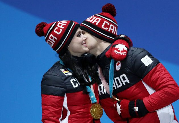 Tessa Virtue and Scott Moir celebrate during the medal ceremony for ice dance figure skating at the 2018