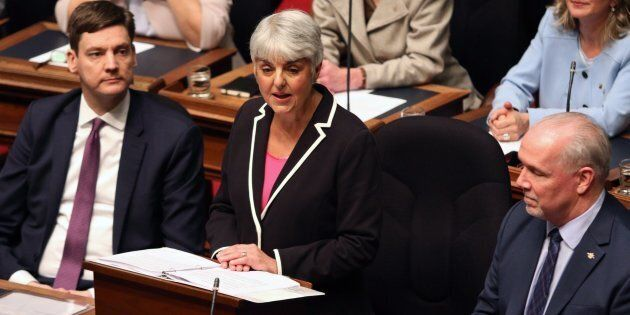 Attorney General David Eby and Premier John Horgan look on as Finance Minister Carole James delivers...