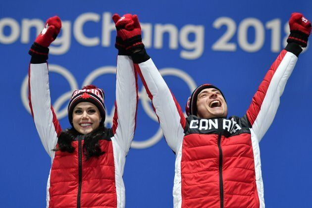 Canada's gold medallists Tessa Virtue and Scott Moir celebrate on the podium at the 2018 Olympics.