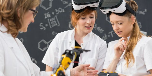 Shot of two students wearing virtual reality glasses and working in a classroom with their teacher